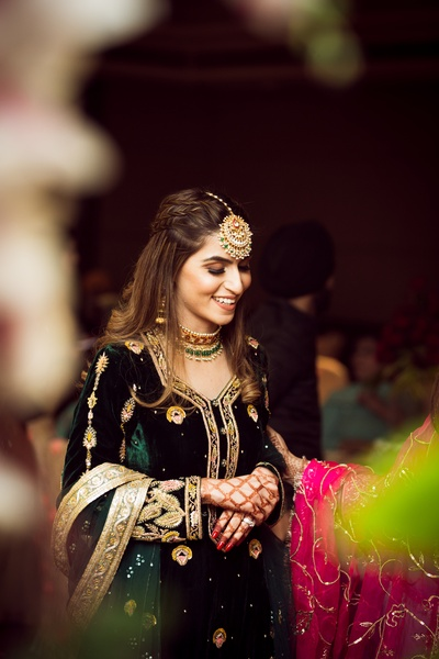 The bride is slaying it in this velvet bottle green outfit with gold embroidery, paired with an oversized maang tikka