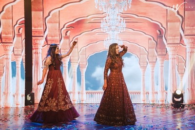 candid capture of the bride and her bridesmaid dancing at the sangeet
