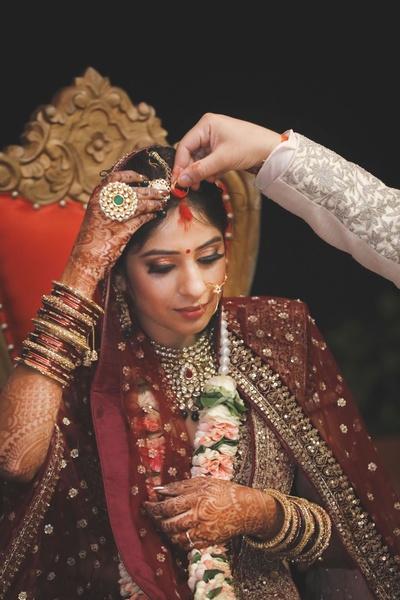The groom puting sindoor onto the bride's forehead.
