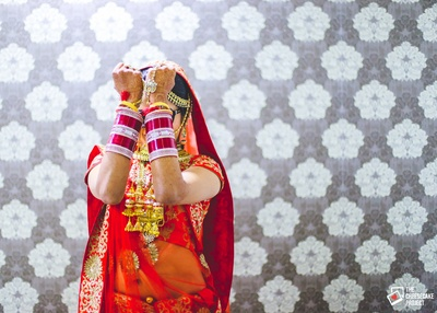 Red wedding lehenga embellished with zari work. Bridal portrait shot against a backdrop of grey wall papers