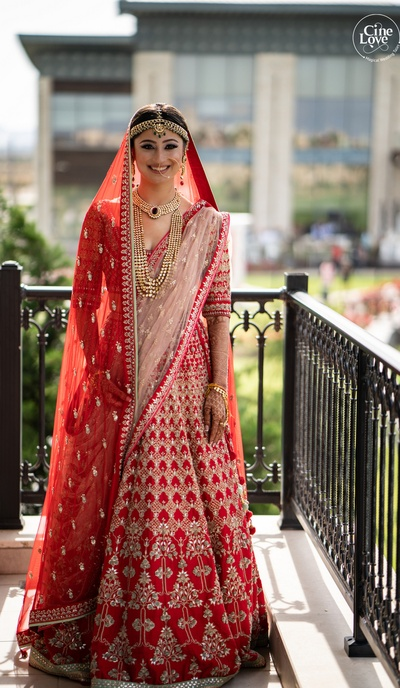 The bride looks radiant in a red traditional embellished lehenga.