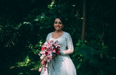 White full-sleeves sheered wedding dress embellished with embroidered bodice styled with a maroon and red bridal bouquet