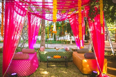 Colorful drape decor and seating arrangement with genga phool hangings for the fun sangeet ceremony!
