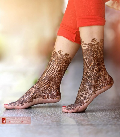 Intricately patterned mehendi designs on the bride's feet