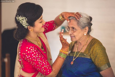Putting bindi for her grandmother for the sangeet ceremony.