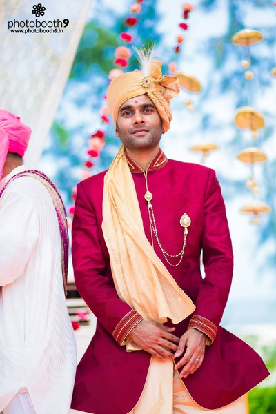 Dressed for the wedding in a maroon sherwani jacket, styled with kundan studded brooch and chain, feather topped Kalgi on a gold Safa
