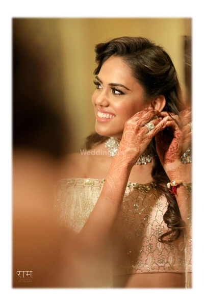 The bride getting ready for her sangeet ceremony in her ivory lehenga