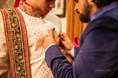 Ivory wedding sherwani styled with red and green sequined dushala