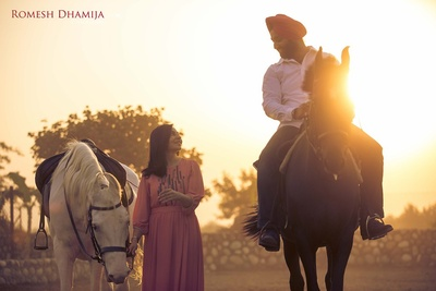 Sunset pre wedding shoot with horses .