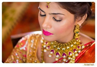 Metallic makeup with bronze eye shadow and hot pink glossy lipstick