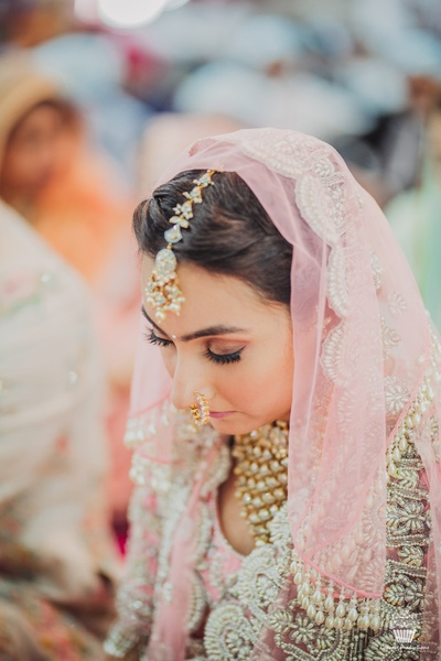 Beautiful bride sitting in the wedding ceremony in a beautiful Manish Malhotra suit