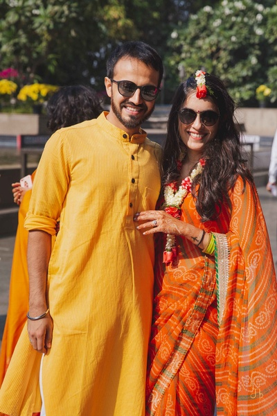 the bride in a orange bandhni saree and groom in a yellow kurta at their haldi ceremony