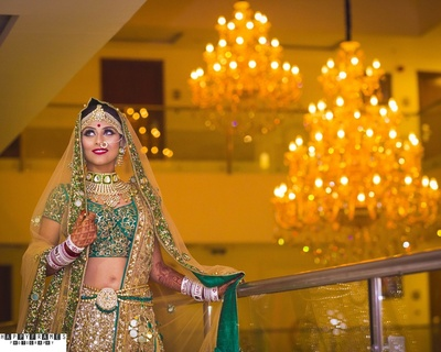 Heavy mirror worked lehenga is styled with kundan jewellery and silver matha patti for wedding