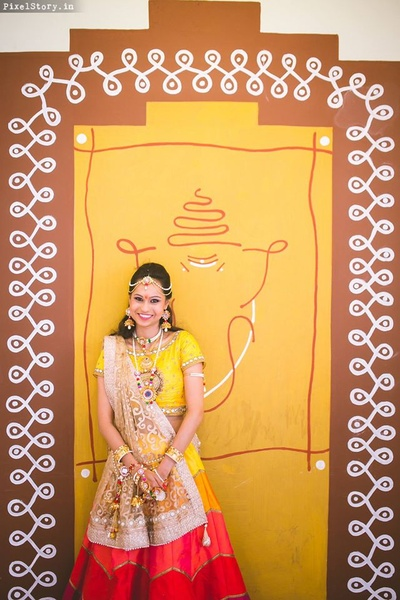 Beautiful Jeenal wearing yellow and red lehenga styled with floral jewellery for the pre wedding rituals.