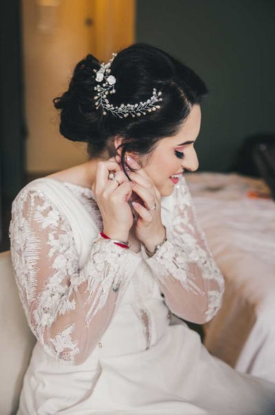 Kanika getting ready for the Christian ceremony in her white bridal gown with lace and net detailing