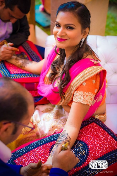 Bronze makeup with bold pink lips - a perfect bridal makeup look for an outdoor mehndi ceremony