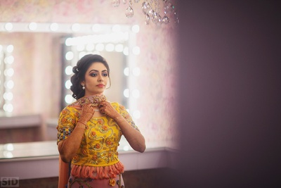 Wearing yellow, peach and pastel pink lehenga by Eshani Studios for the Sangeet Ceremony.