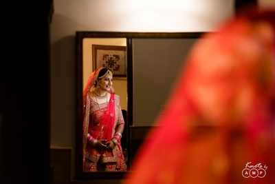 The bride looks stunning in this fuschia pink heavily embellished lehenga.
