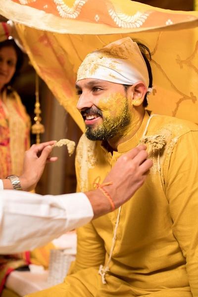 The groom wears an understated yellow kurta for his haldi ceremony.