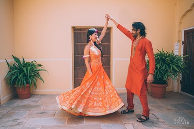 Groom wearing coral colored kurta and matching chooridar for the mehendi ceremony