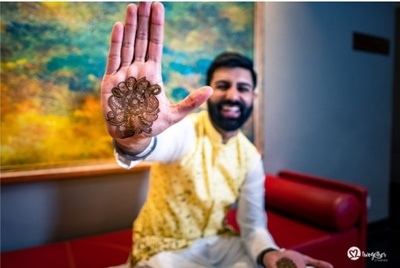 The groom showing off his mehendi design!