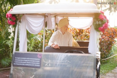 The groom entering the venue in a golf car