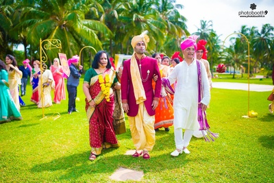 Dressed for the wedding in a maroon sherwani jacket with chained brooch and a gold dhoti, safa and matching mojris