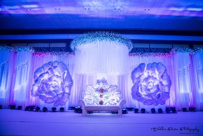 Reception stage adorned with real flowers, glass like chandeliers and royal two seat sofa