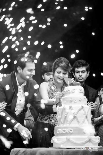 A magical black and white capture of the 5 tiered fondant cake for engagement ceremony with an engagement ring topper