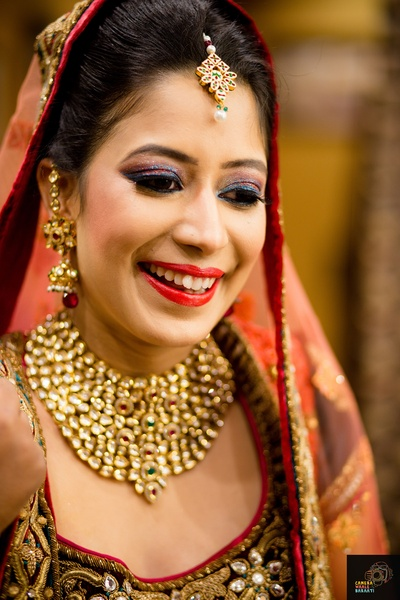Red and green bridal lehenga styled with striking bridal eye shadow