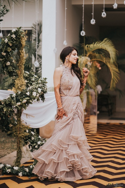 The bride looks stunning in this light beige ruffled saree gown.