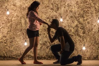 Romantic pre-wedding photoshoot with lightbulbs illuminating the background