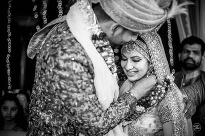 The groom tying the mangalsutra around the bride's neck