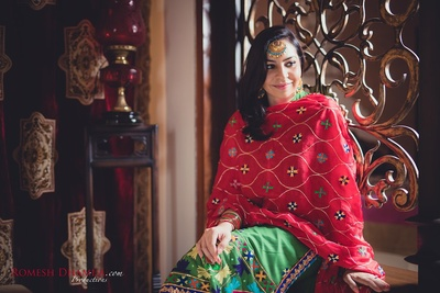Dressed up in colorful phulkari salwar suit styled with maangtikka and jumkas for the mehendi ceremony.