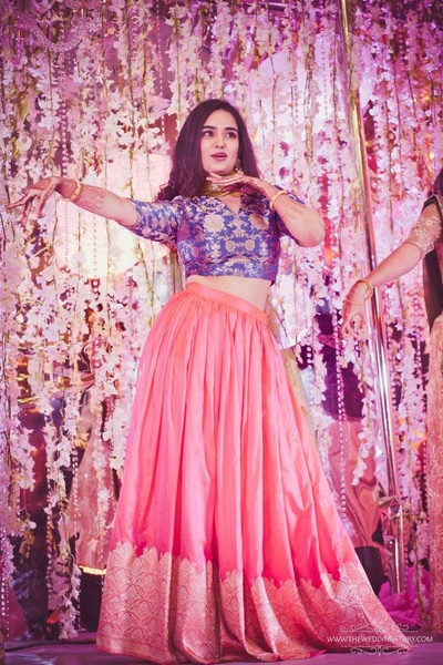 Sister of the bride in a pink and blue Benarasi lehenga for the sangeet ceremony