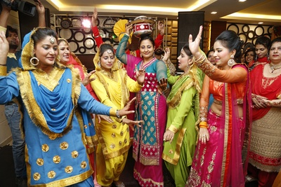Guests wearing colorful punjabi suits dancing to celebrate the happy couple