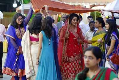 Bride being escorted by family members under a red bridal canopy