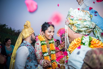 Varmala exchange between the bride and groom at the wedding mandap
