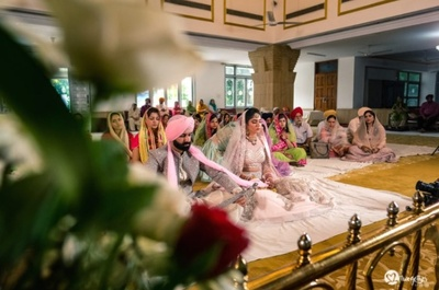 The couple in prayer during their Anand Karaj wedding!