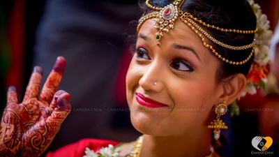 Bride's graceful expressions beautified with nose stud, gold jhumkas and layered Maathapatti
