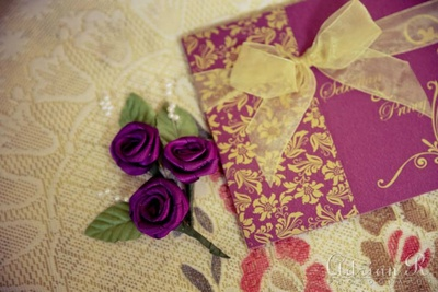 Elegant flower designed purple and gold wedding invitation with a gold tissue front bow