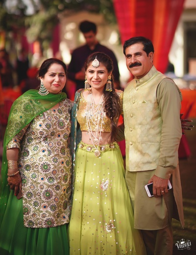 Bride in a green lehenga captured in a beautiful picture with family
