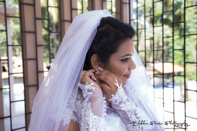 Hand gloves adorned with lace along with a sheer net veil