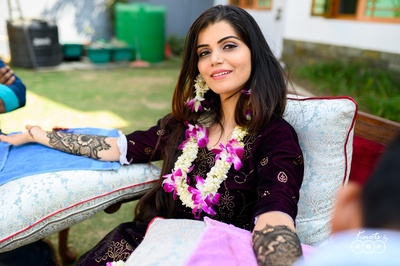 Ain looking gorgeous dressed in a deep purple outfit and accessorized with floral jewellery.