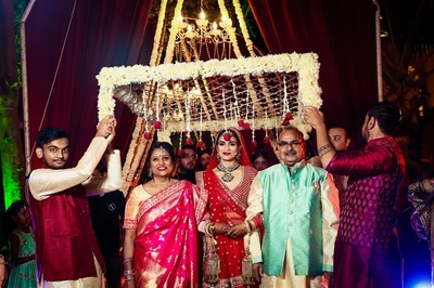 The bride enters with a phoolon ki chaddar over her, in traditional style!