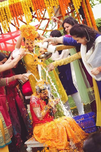 Bride drenched in haldi, milk and flower rain on her haldi ceremony held at Hotel Bristol.