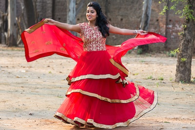 Flared red layered lehenga with a golden border and a resham work bodice, paired with a matching sheer embellished dupatta