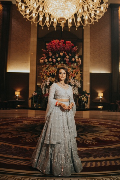 The bride looks absolutely striking in a silver shimmery lehenga.
