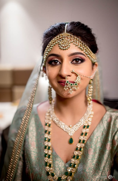 Bridal portrait of Tanvi in her blue-grey blouse ad contrasting emerald and diamond jewellery