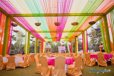 Vibrant drapes setup in hues of fuchsia, coral and mint green drapes, upturned umbrellas, hangings and table covers